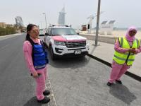 Pilipino doctor Maria Lagbes (L) and a driver stand next to a pink ambulance of the Women Responders team in Dubai. / AFP PHOTO / GIUSEPPE CACACE