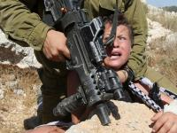 An Israeli soldier arresting a n 11-year-old Palestinian boy.
